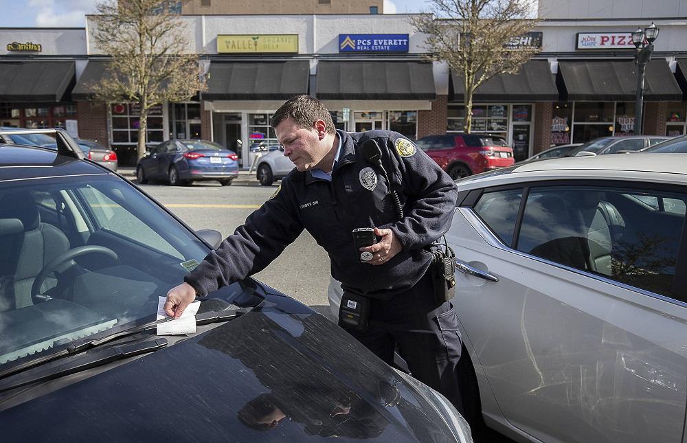 Полицейский выписывает штраф за парковку