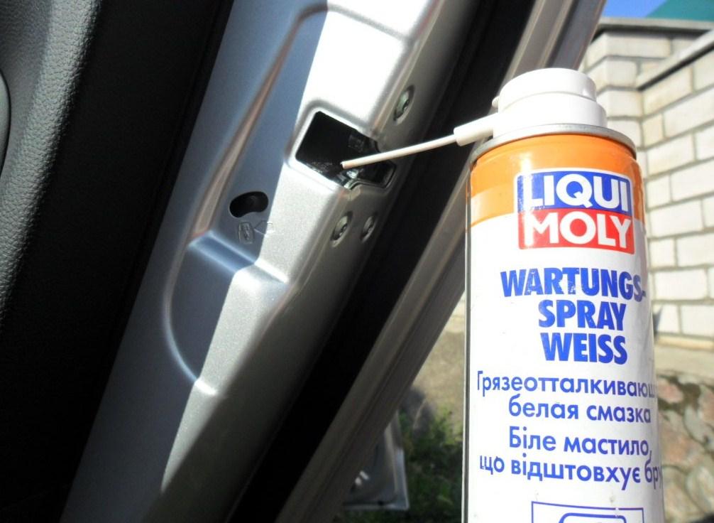 Процесс смазки дверных петель на автомобиле
