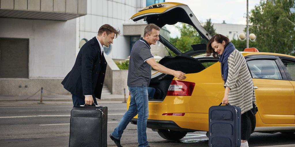 Водитель помогает пассажиру разместить багаж